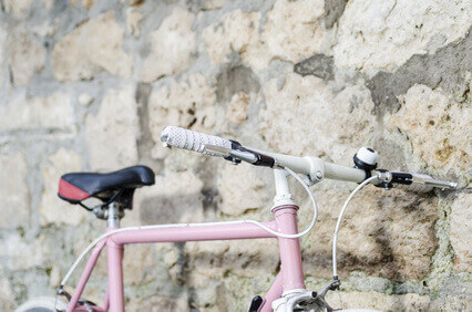 Pink vintage Bicycle with white wheels, leaning against a Stone
